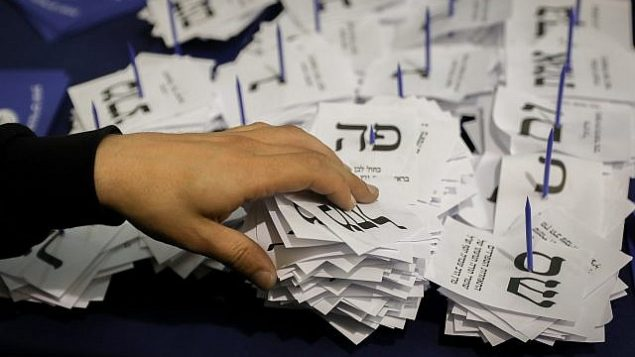 مسؤولون يقومون بفرز بطاقات الاقتراع الأخيرة من الجنود والغائبين في الكنيست في القدس، بعد يوم من الإنتخابات العامة، 10 أبريل، 2019.  (Noam Revkin Fenton/Flash90)