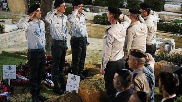 جنود إسرائيليون يؤدون التحية العسكرية بالقرب من قبر زخاريا باومل، خلال جنازته في المقبرة العسكرية في جبل هرتسل، القدس، 4 أبريل، 2019. (Hadas Parush/Flash90)