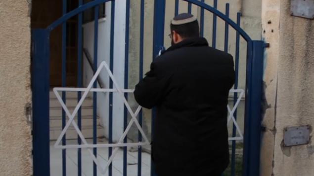 """الحاخام الراحل أحيعاد إيتنغر عند بوابة المدرسة الدينية """"عوز إمونا"""" في تل أبيب، 2017 (YouTube screenshot)"""