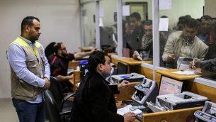 موظفو بريد يساعدون فلسطينيين وصلوا إلى مكتب البريد الرئيسي في مدينة غزة في 26 يناير، 2019 للحصول على أموال مساعدات من الحكومة القطرية للعائلات المحتاجة. (Mahmud Hams/AFP)