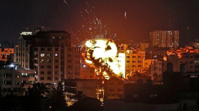 انفجار بين مبان خلال غارة جوية إسرائيلية على القطاع الساحلي ردا على إطلاق صواريخ من القطاع، 4 مايو، 2019.  (Mahmud Hams / AFP)