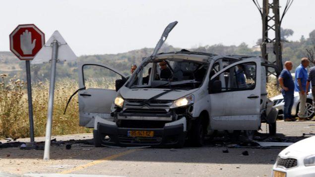 اسرائيليون يتجمعون بالقرب من سيارة اصيبت بصاروخ مضاد للدبابات اطلق من شمال قطاع غزة، ما ادى الى مقتل السائق، بالقرب من ياد مردخاي في جنوب اسرائيل، 5 مايو 2019 (Jack GUEZ / AFP)