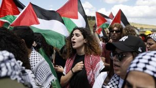 عرب من مواطني إسرائيل يرفعون الأعلام الفلسطينية خلال مشاركتهم في 'مسيرة العودة' السنوية التي تجرى بالتزامن مع احتفال إسرائيل باستقلالها، بالقرب من مدينة أم الفحم في شمال البلاد، 9 مايو، 2019. (Ahmad Gharabli/AFP)