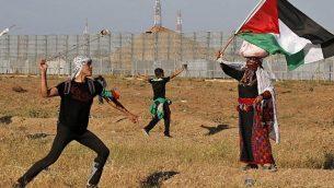 متظاهر فلسطيني يرشق القوات الإسرائيلية بحجارة وامراة ترتدي زيا فلسطينيا تقليديا تلوح بالعلم الفلسطيني، خلال تظاهرة بالقرب من الحدود مع إسرائيل، شرق مدينة غزة، 10 مايو، 2019. (Said KHATIB / AFP)