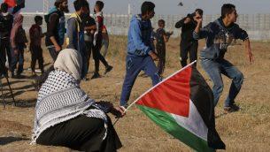 متظاهر يرشق حجارة باتجاه جنود اسرائيليين بينما تحمل امرأة علم فلسطين، خلال مظاهرة بالقرب من الحدود مع اسرائيل، شرقي مدينة غزة، 10 مايو 2019 (Said KHATIB / AFP)