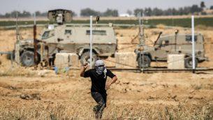 متظاهر فلسطيني يستخدم مقلاع لرشق حجارة باتجاه جنود اسرائيليين خلال مظاهرات يوم النكبة شرقي خان يونس، جنوب قطاع غزة، 15 مايو 2019 (Thomas COEX / AFP)