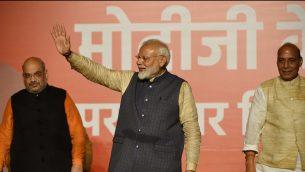 رئيس الوزراء ناريندرا مودي (وسط الصورة) يحيي مناصريه وإلى جانبه يقف رئيس حزب 'بهاراتيا جانتا'، أميت شاه (على يسار الصورة) ووزير الشؤون الداخلية الهندي، راجنات سينغ، خلال احتفالهم بالنصر في الانتخابات العامة في الهند في مقر الحزب في نيودلهي، 23 مايو، 2019.  ( PRAKASH SINGH / AFP)