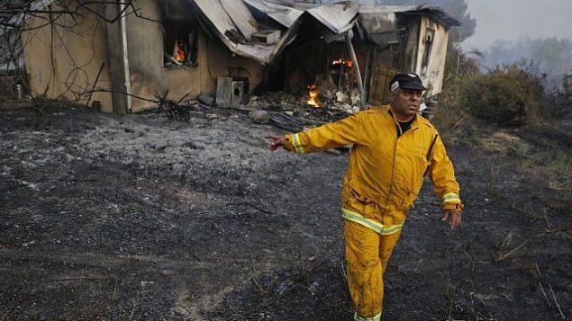 رجل إطفاء يمر من أمام منزل محترق في خضم موجة حر شديدة في كيبتوس هرئيل بوسط إسرائيل، 23 مايو، 2019. (Ahmad GHARABLI / AFP)