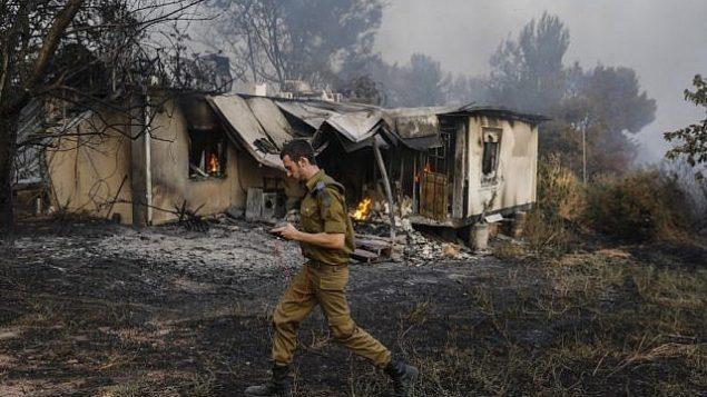 جندي إسرائيلي يمر من أمام منزل محترق في خضم موجة حر شديدة في كيبتوس هرئيل بوسط إسرائيل، 23 مايو، 2019. (Ahmad GHARABLI / AFP)