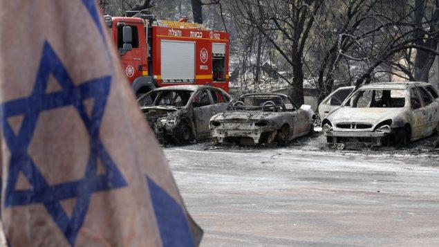 صورة لعلم اسرائيلي امام سيارات تضررت في اعقاب حريق وسط موجة حر في قرية ميفو مودعين، في مركز اسرائيل، 24 مايو 2019 (JACK GUEZ / AFP)