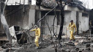رجال اطفاء يفحصون منزلا تضرر نتيجة حريق جاء خلال موجة حر شديد في قرية ميفو مودعيم، في مركز اسرائيل، 24 مايو 2019 (JACK GUEZ / AFP)