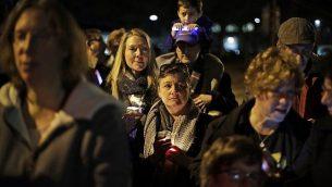 أشخاص يشاركون في إضاءة شمعدان خارج كنيس 'شجرة الحياة' في الليلة الأولى لعيد الحانوكاه، 2 ديسمبر، 2018، في حين 'سكويرل هيل' في مدينة بتيسوبورغ الأمريكية، حيث قام مسلح بقتل 11 شخصا خلال الصلاة في 27 أكتوبر، 2018 في الكنيس.  (AP Photo/Gene J. Puskar)