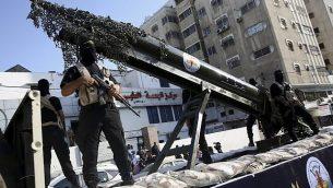 عناصر في 'سرايا القدس'، الجناح العسكري لحركة الجهاد الإسلامي الفلسطينية، خلال مسيرة مع مجسم صاروخ على شاحنة في 4 أكتوبر، 2018.  (AP Photo/Adel Hana)