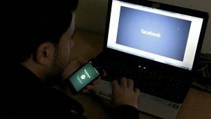 صورة توضيحية لرجل يجلس أمام شاشة كمبيوتر يظهر عليها شعار 'فيسبوك'، 26 فبراير، 2014.(Abed Rahim Khatib/Flash90)