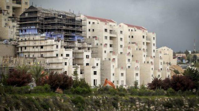 أعمال بناء في مستوطنة كريات أربع في الضفة الغربية، بالقرب من مدينة الخليل، 2 أبريل، 2017. (Wisam Hashlamoun/Flash90)