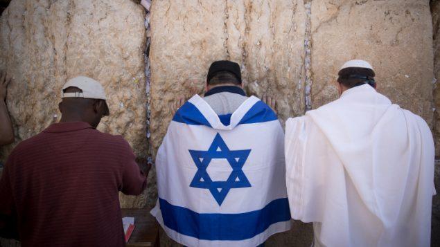 رجل يرتدي علم اسرائيل اثناء الصلاة في حائط المبكى في القدس القديمة، 17 سبتمبر 2017 (Yonatan Sindel/Flash90)