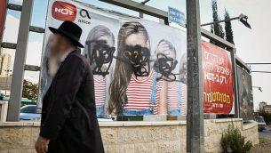 رجل حريدي يمر من أمام لافتة إعلانية تم إتلافها في القدس حيث تم تغطية وجوه النساء فيها، 2 نوفمبر، 2017. (Noam Revkin Fenton/Flash90)