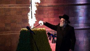 الناجي من المحرقة وحاخام اسرائيل الرئيسي السابق مئير لاو يشعل شعلة خلال مراسيم في متحف ياد فاشيم في القدس، في يوم ذكرى المحرقة الإسرائيلي، 11 ابريل 2018 (Yonatan Sindel/Flash90)