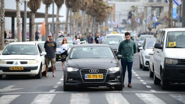 اسرائيليون واقفون خلال صفارة مدتها دقيقتين لإحياء ذكرى ضحايا المحرقة في يوم ذكرى المحرقة الإسرائيلي، في تل ابيب، 2 مايو 2019 (Tomer Neuberg/Flash90)