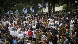 إسرائيليون يقفون دقيقتي صمت بالقرب من قبور جنود إسرائيليين في المقبرة العسكرية في جبل هرتسل بالقدس، مع سماع دوي صفارات الإنذار في جميع أنحاء إسرائيل، إحياءا ليوم ذكرى قتلى الجيش الإسرائيلي وضحايا الهجمات، 8 مايو، 2019.  (Hadas Parush/Flash90)