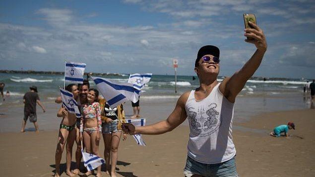 إسرائيليون في شاطئ 'بوغراشوف' في تل أبيب يتفرجون على العرض الجوي العسكري في إطار احتفالات إسرائيل بيوم إستقلالها ال71.(Hadas Parush/Flash 900)