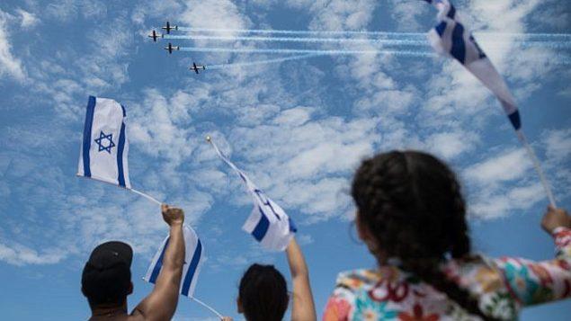 إسرائيليون في شاطئ 'بوغراشوف' في تل أبيب يتفرجون على العرض الجوي العسكري في إطار احتفالات إسرائيل بيوم إستقلالها ال71.(Hadas Parush/Flash 90)