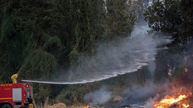 رجال الإطفاء يحاولون إخماد حريق بالقرب من كيبوتس هرئيل، 23 مايو، 2019.  (Yonatan Sindel/Flash90)
