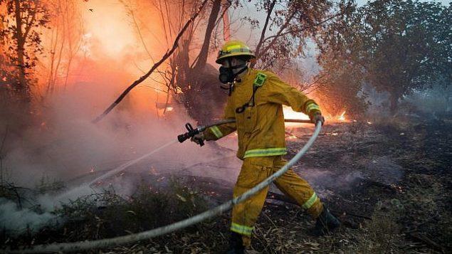 توضيحية: رجال الإطفاء يحاولون إخماد حريق بالقرب من كيبوتس هرئيل، 23 مايو، 2019. (Yonatan Sindel/Flash90)