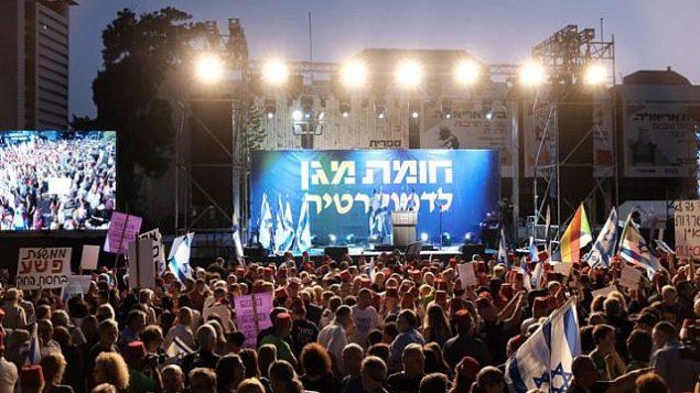 متظاهرون اسرائيليون يشاركون في مظاهرة ضخمة ضد رئيس الوزراء بنيامين نتنياهو تحت شعار 'وقف قانون الحصانة - درع واقي للديمقراطية' في تل ابيب، 25 مايو 2019 (Tomer Neuberg/Flash90)
