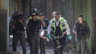 قوات امن ومسعفون يخلون جقمان رجل فلسطيني طعن شخصين في القدس القديمة، 31 مايو 2019 (Yonatan Sindel/Flash90)