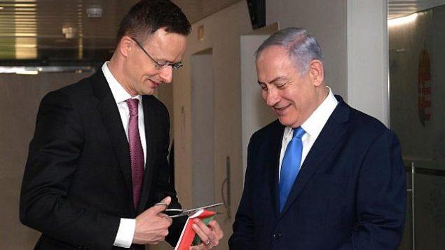 وزير الخارجية المجري بيتر سيارتو ورئيس الوزراء بنيامين نتنياهو بفتتحان مكتب التجارة المجري في وسط القدس، 19 مارس، 2019. (Amos Ben Gershom/GPO)