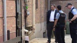 عناصر الشرطة والحاخام ديفيد وولكنفيلد يحققون في ما يُشتبه بهجوم حرق عمد خارج كنيس 'أنشي شلوم بني إسرائيل' في شيكاغو، 19 مايو، 2019.  (screen capture: Fox32 Chicago)