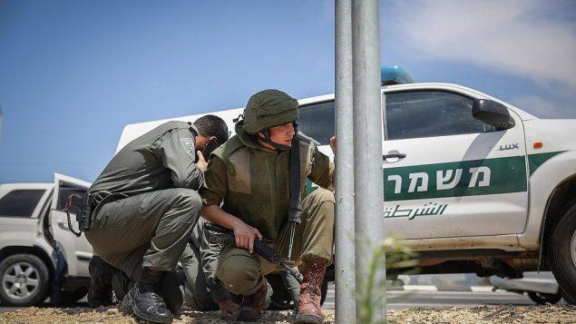 عناصر قوات امن اسرائيليون يختبئون في طرف طريق قريب من حدود غزة، عند انطلاق صفارات انذار صاروخي، 5 مايو 2019  Noam Rivkin Fenton/Flash90)
