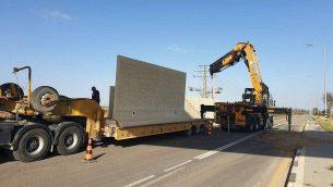 عمال ينصبون جدار على جانب طريق بالقرب من كيبوتس ايريز في جنوب اسرائيل لحمايته من الصواريخ، 8 مايو 2019 (Courtesy)
