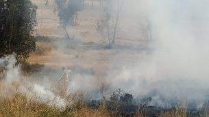 رجال اطفاء يحاولون اخماد حريق في منطقة اشكول في جنوب اسرائيل، نتج عن بالون حارق اطلق من قطاع غزة، 22 مايو 2019 (Eli Cohen/Fire and Rescue Services)