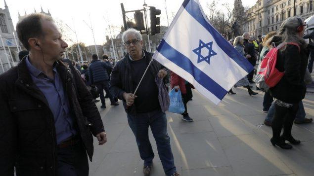 أعضاء من المجتمع اليهودي في تظاهرة ضد زعيم حزب 'العمال' البريطاني المعارض، جيريمي كوربين ومعاداة السامية في حزبه، من امام البرلمان البريطاني وسط لندن، 26 مارس، 2018. (AFP PHOTO / Tolga AKMEN)