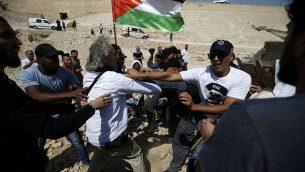 قوات الأمن الإسرائيلية تشتبك مع المتظاهر الأمريكي-الفرنسي فرانك رومانو في 14 سبتمبر، 2018، خلال مظاهرة ضد الهدم المتوقع لقرية الخان الأحمر في الضفة الغربية. (AFP/Abbas Momani)