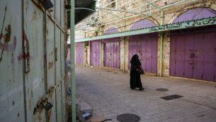 سيدة فلسطينية تمشي بين متاجر مغلقة خلال اضراب احتجاجا على قانون الضمان الاجتماعي الذي اقترحته السلطة الفلسطينية، في مدينة الخليل في الضفة الغربية، 15 يناير 2019 (HAZEM BADER / AFP)