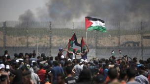 متظاهرون فلسطينيون يتجمعون شرقي مدينة غزة، خلال مظاهرة في الذكرى ال71 للنكبة، 15 مايو 2019 (Mahmud Hams/AFP)
