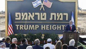 """رئيس الوزراء بنيامين نتنياهو يلقي بخطاب أمام لافتة البلدة الجديدة """"رمات ترامب"""" أو """"هضبة ترامب"""" بالعربية، على اسم الرئيس الأمريكي دونالد ترامب خلال مراسم رسمية في هضبة الجولان، 16 يونيو، 2019. (Jalaa MAREY / AFP)"""