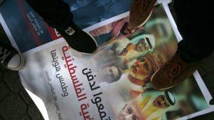 فلسطينيون يدوسون على لافتة تظهر صور ولي عهد ابو ظبي الشيخ محمد بن زايد، ولي العهد السعودي محمد بن سلمان، العاهل البحريني حند ال خليفة، سلطان قابوس العماني، رئيس الوزراء بنيامين نتنياهو، الرئيس الامريكي دونالد ترامب وصهره ومستشاره جاريد كوشنر، خلال مظاهرة ضد مؤتمر 'السلام الى الازدهر' الامريكي في البحرين، في مدينة غزة، 24 يونيو 2019 (MOHAMMED ABED / AFP)