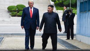 الرئيس الامريكي دونالد ترامب ورئيس كوريا الشمالية كيم جونغ أون، يعبران خط الحدود العسكرية في المنطقة العازلة بين الكوريتين، 30 يونيو 2019 (Brendan Smialowski / AFP)