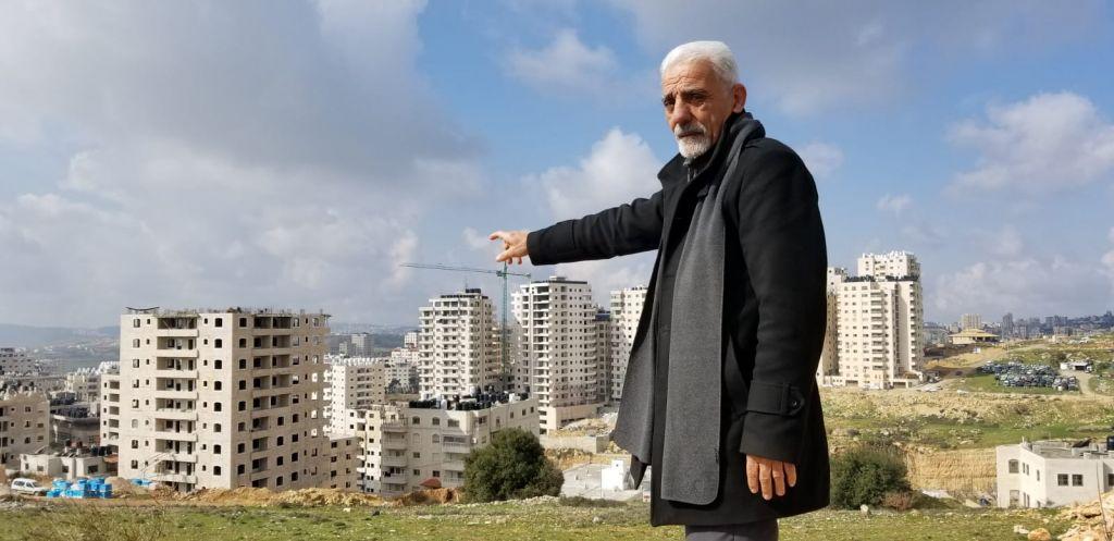 الناشط منير زغاير، الذي يترأس لجنة تقدم بانتظام شكاوى لبلدية القدس حول وضع الخدمات في كفر عقب، يشير إلى عدد من المباني في الحي التي تم بناؤها بشكل يتعارض مع المعايير، 20 فبراير، 2019. (Adam Rasgon/Times of Israel)