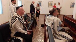 مصلون، من ضمنهم مبعوث الإدارة الأمريكية للشرق الأوسط، جيسون غرينبلات (يسار، جالس على المقعد) يشاركون في صلاة صباحية أقيمت في كنيس في العاصمة البحرينية المنامة، 26 يونيو، 2019. (Raphael Ahren/Times of Israel)