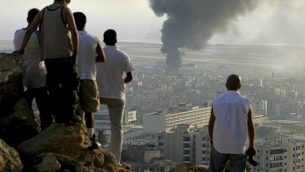 في هذه الصورة من تاريخ 14 يوليو، 2006، يظهر شبان لبنانينون يقفون على قمة تل يطل على مدينة بيروت في لبنان عند غروب الشمس لمشاهدة الدخان المتصاعد من مضخة وقود في مطار بيروت الدولي، الذي تعرض لغارة جوية إسرائيلية. (AP Photo/Ben Curtis)