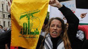 متظاهرة مناصرة للفلسطينيين ترفع علم منظمة 'حزب الله'، خلال مظاهرة مناهضة لإسرائيل في وسط لندن، الإثنين، 31 مايو، 2010.  (AP Photo/Lefteris Pitarakis)