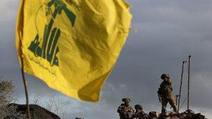 في هذه الصورة من 13 ديسمبر، 2018، جنود إسرائيليون يقومون بالحراسة بالقرب من كاميرات في موقعهم الجديد أمام علم لمنظمة 'حزب الله'، بالقلاب من قرية ميس الجبل على الحدود الجنوبية للبنان، (AP Photo/Hussein Malla)
