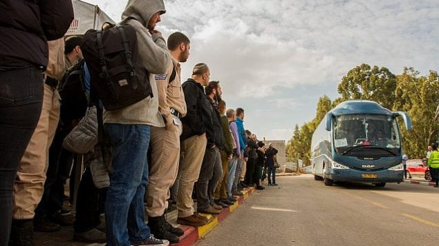 إسرائيليون في انتظار الحافلات إلى تل أبيب في محطة القطار في بيت يهوشواع، 9 فبراير، 2018. (Flash90)