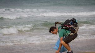 المدون الإسرائيلي غيل دوري يلتقط كيس بلاستيك في شاطئ بيت يناير في 23 نوفمبر 2018، خلال رحلته لمدة 9 ايام لرفع الوعي حول اثار تلويث البلاستيك في البحر المتوسط (Meir Vaknin/Flash90)