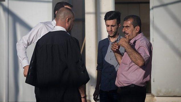 المحامي ناشف درويش (على يسار الصورة) يتحدث مع شقيق ونجل محمود قطوسة، الرجل الفلسطيني المتهم باختطاف واغتصاب طفلة إسرائيلية في السابعة من عمرها، في المحكمة العسكرية بمنطقة يهودا، 19 يونيو، 2019. (Yonatan Sindel/Flash90)